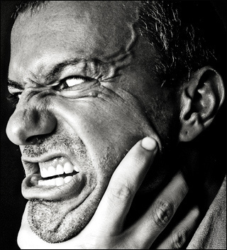 Photo of a man's face in a grimace of rage with a hand around the throat.