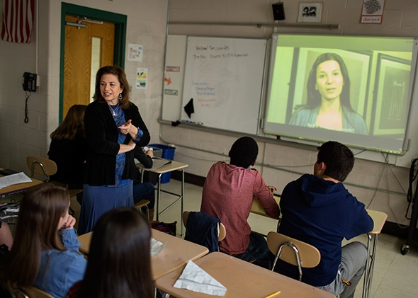 Photo of teacher standing in front of class, talking to students, with projected video in the background.