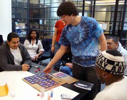 Photo of several students around a table with a board game.