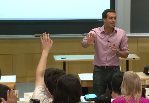 Photo of instructor at the front of class, with students raising hands.