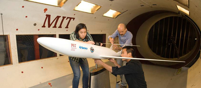 A woman and two men examine and take measurements of a model jet inside a wind tunnel.