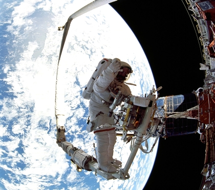 Photo of an astronaut in spacesuit standing on a platform in space.