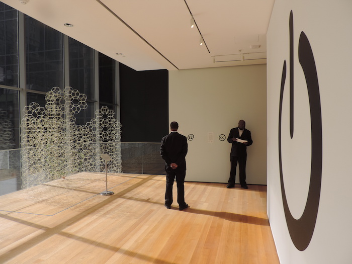 Photo of a museum exhibit hall, with the on/off symbol and Creative Commons logos on the wall.