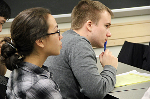 Three students sitting at a table; female student looks toward speaker at front of room; male student leans forward, holds pen, and looks toward speaker; another male student looks down at paper.