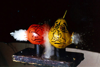 Photo of two pieces of fruit side-by-side, with a bullet exiting.