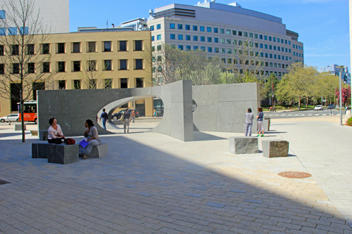 Photo of granite sculpture with a few people nearby.