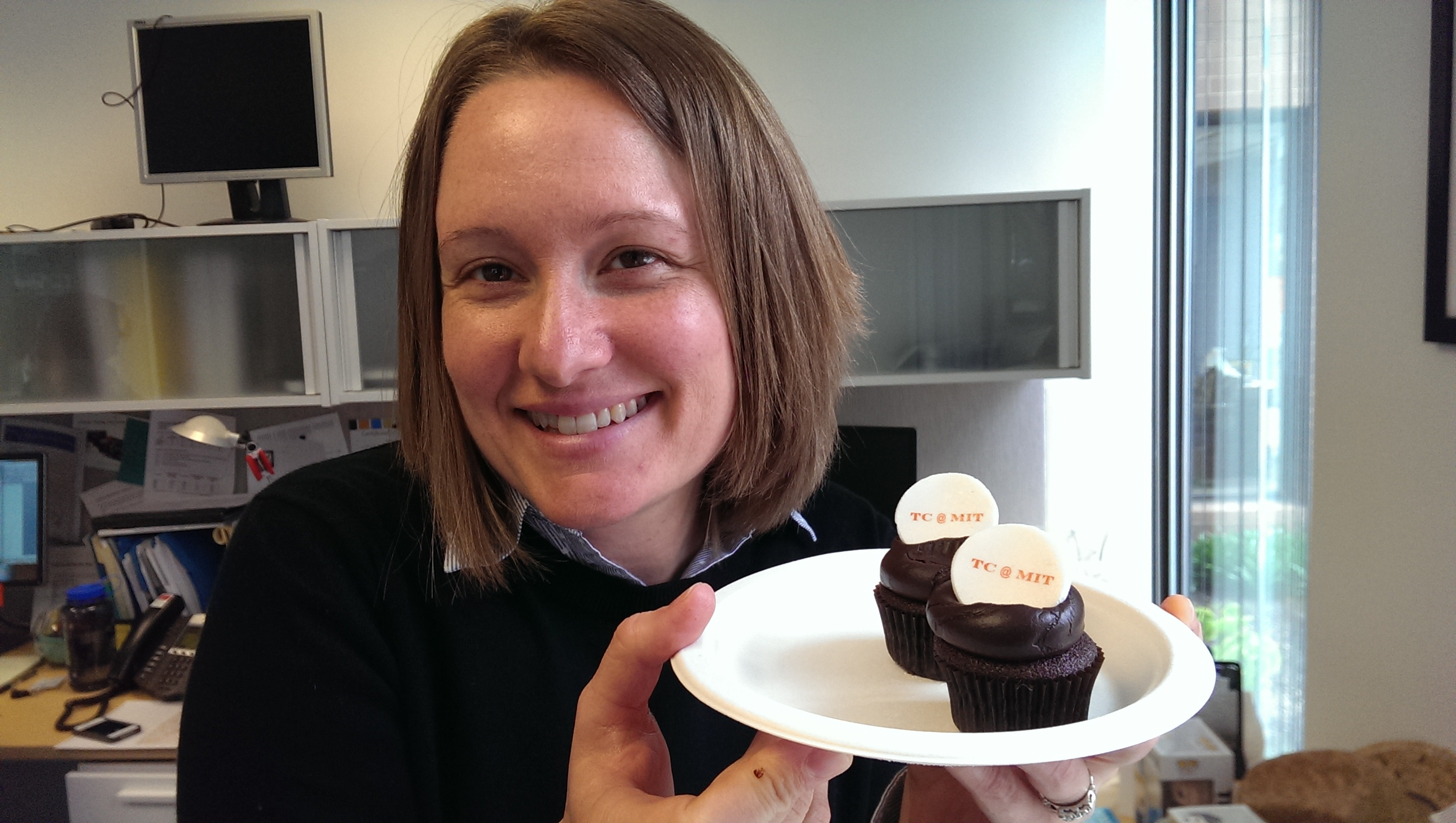 Photo of a smiling woman holding a plate with two cupcakes