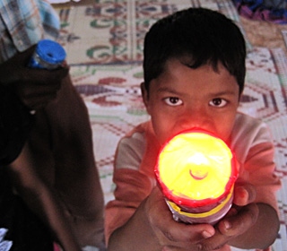 A young boy pointing a shining flashlight at the camera.