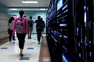 Photo of students walking down a school hallway, with a bank of electronic devices on their right.