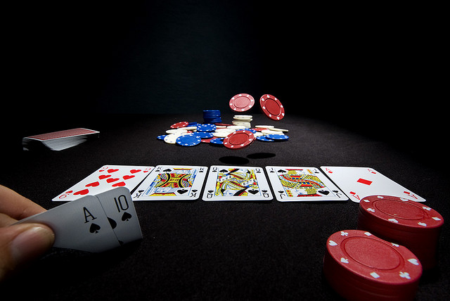 Photo of cards and poker chips laid out on table, with a ace high straight flush in a player's hand.