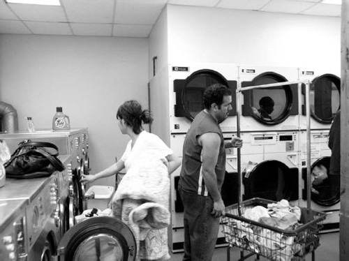 Photo of two people in a laundromat facing away from each other.