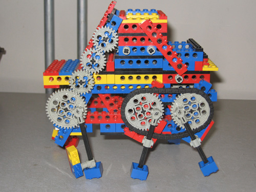 A six-legged walking robot, from the side, showing the gears that move the legs.