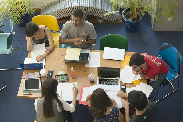 Photo of several students working together around a table.