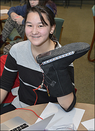 Photo of a girl holding up a boot to which she has added a sensor, processor, and flashing lights.