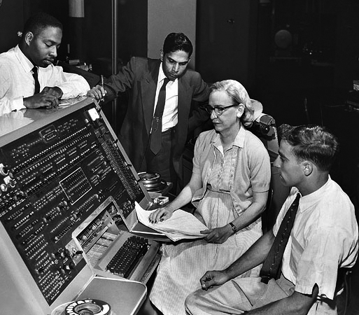 A black and white photograph circa 1960 with four people gathered around the UNIVAC I keyboard, which was the first commercial electronic computer.