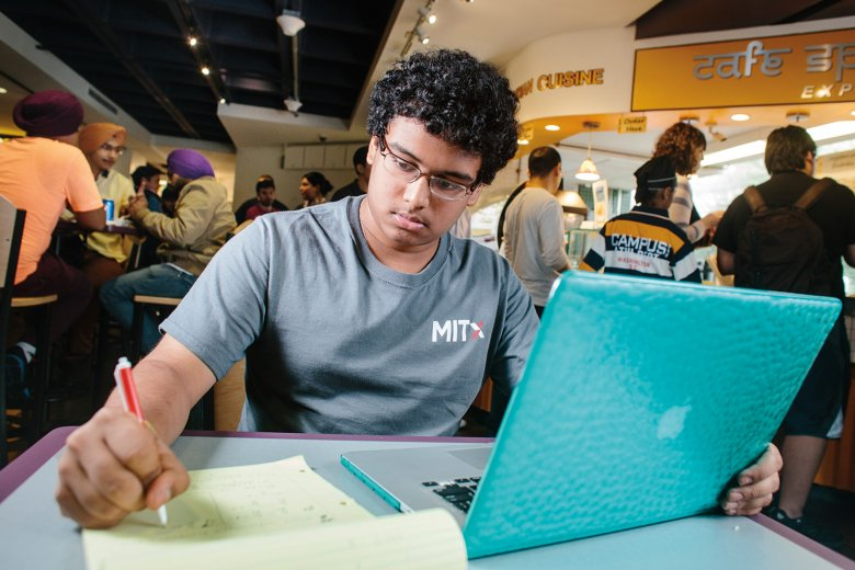 Photo of young man working at a table in MIT dining area with his laptop, writing in a notebook.