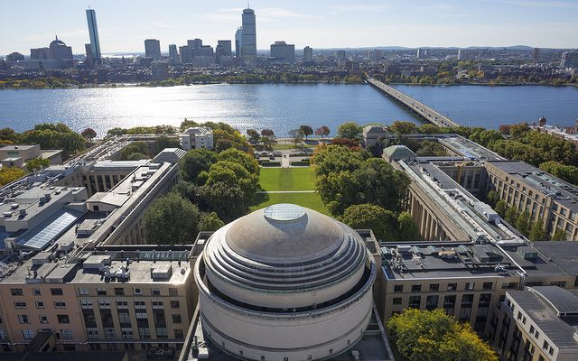 Aerial photo of the MIT dome and other nearby buildings, with the Charles River and Boston skyline in the background.