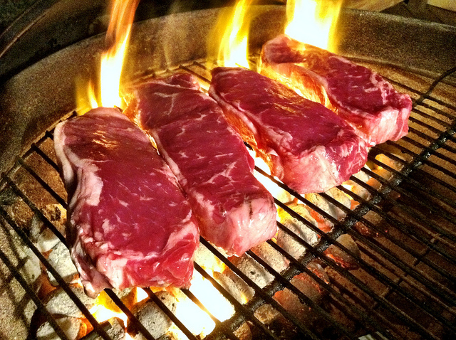 Photo of four steaks cooking over an open fire.