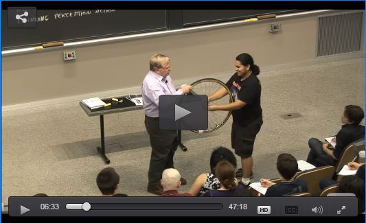 Screengrab of professor with student at front of classroom, holding a bicycle wheel.