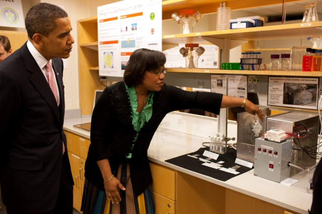 Photo of woman pointing out aspects of aparatus on a lab bench, with President standing beside her looking on.