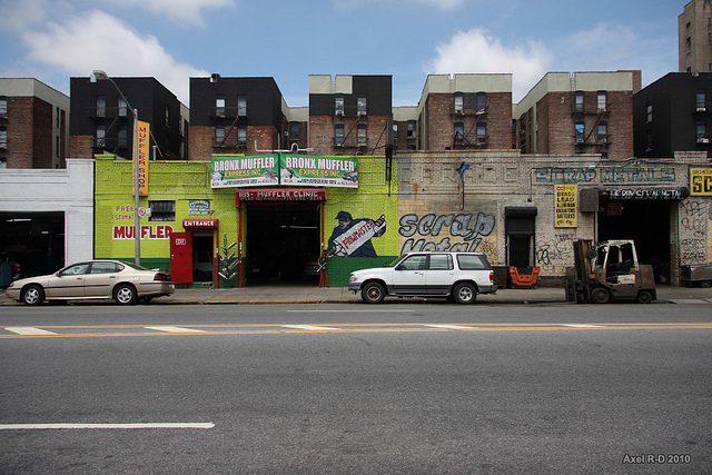 Photo of urban street scene, with brightly painted front of an auto muffler shop.
