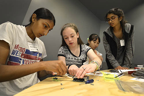 Photo of several girls around a table working on some electronics.
