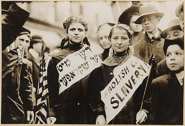 """Photo from 1909 showing two girls wearing banners that read """"ABOLISH CHILD SLAVERY"""" in english and yiddish."""