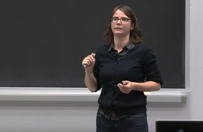 Screenshot from video, of woman speaking in front of a chalkboard, holding a laser pointer.