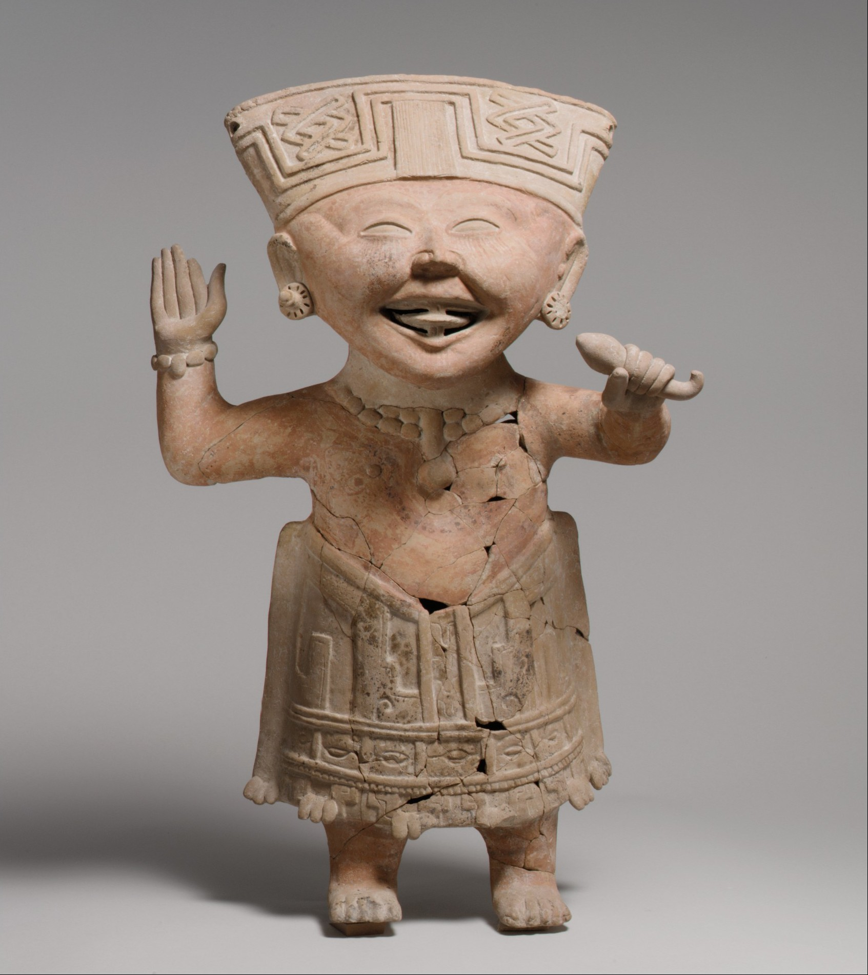 Photo of ceramic statue of a person, smilling with arms upraised.