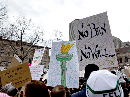 "Photo of protesters gathered in a public square, featuring a sign reading ""No Ban, No Wall."""