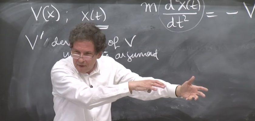 Male professor gesturing in front of a chalkboard.