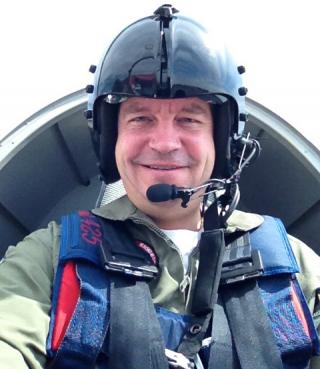 Photo of man sitting in an airplane cockpit, wearing a helmet.