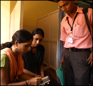 A female health worker logs data on a handheld device as two others look on.