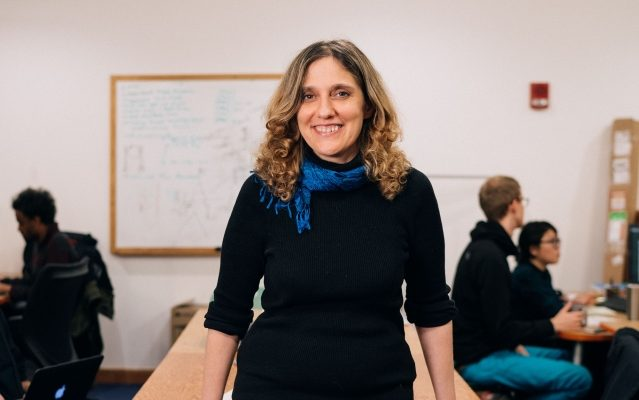 Photo of Regina Barzilay relaxing against a table in classroom, with students working in the background.