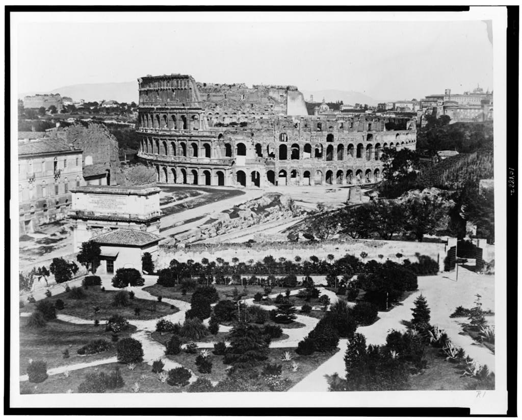 Black-and-white photo of the Rome Colosseum in its landscape, highlighting the partially collapsed walls.