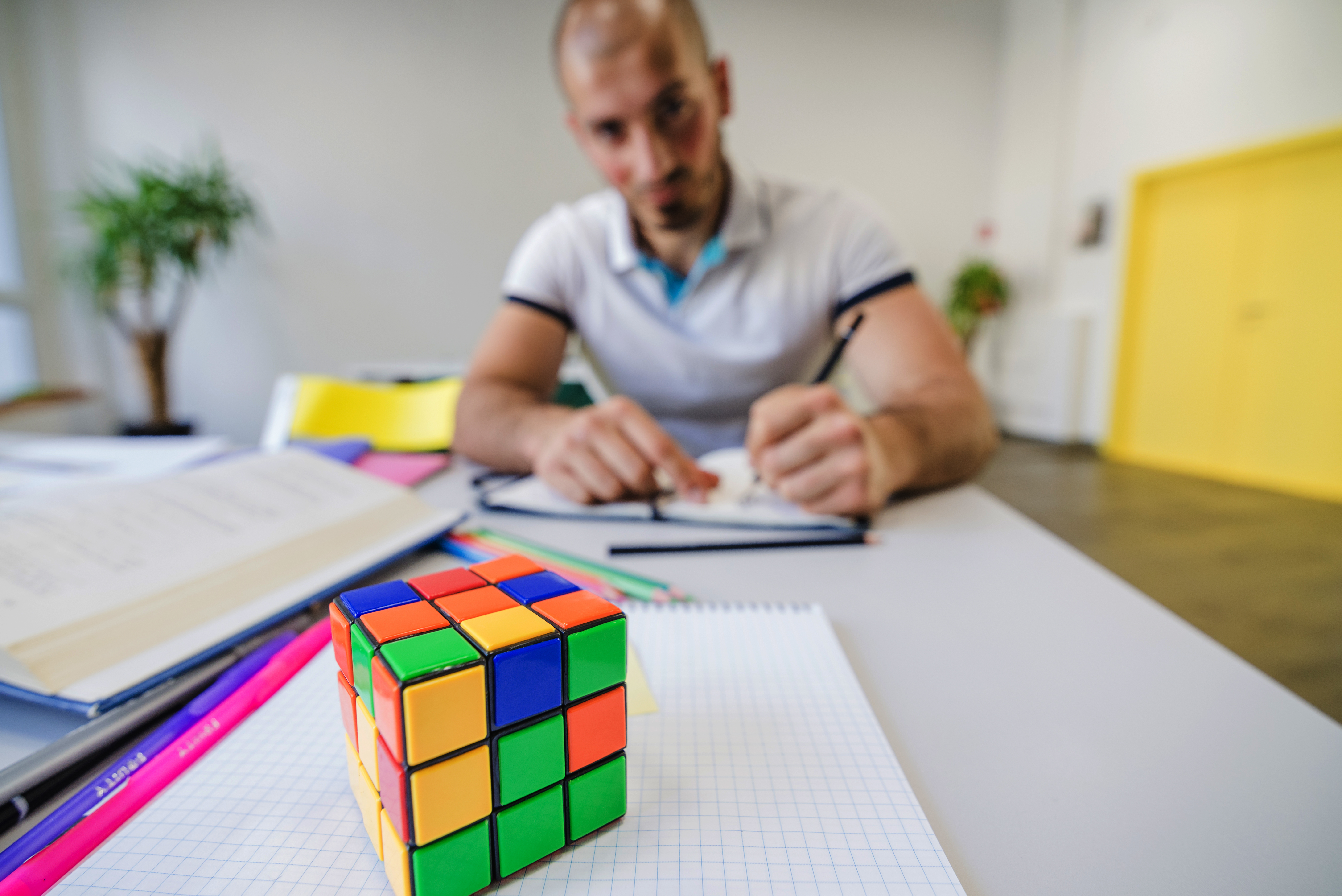 Photo of Rubik's Cube on a table, with a man sitting behind it and looking at it.