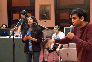 Photo of two singers on microphones with a recording engineering in the background.
