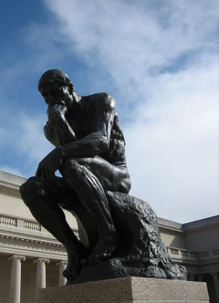 Photo of seated man sculpture in front of a museum building.