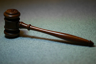 Photo of a wooden gavel on a tabletop.