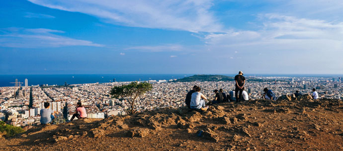 Photo of several people on a hilltop looking over a city, with the ocean in the distance.