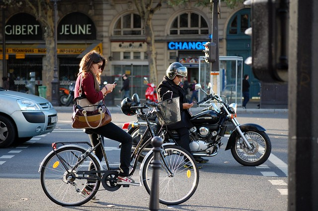 A woman on a bicycle and a man on a motorcycle, both looking at their mobile phones while they are stopped in traffic