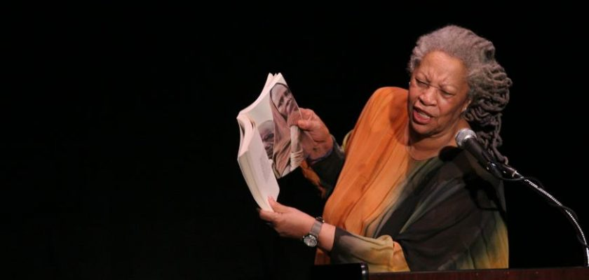 An older African-American woman holding a book open to read aloud